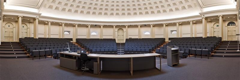 Zicht op een leeg halfrond auditorium met blauwe zitjes