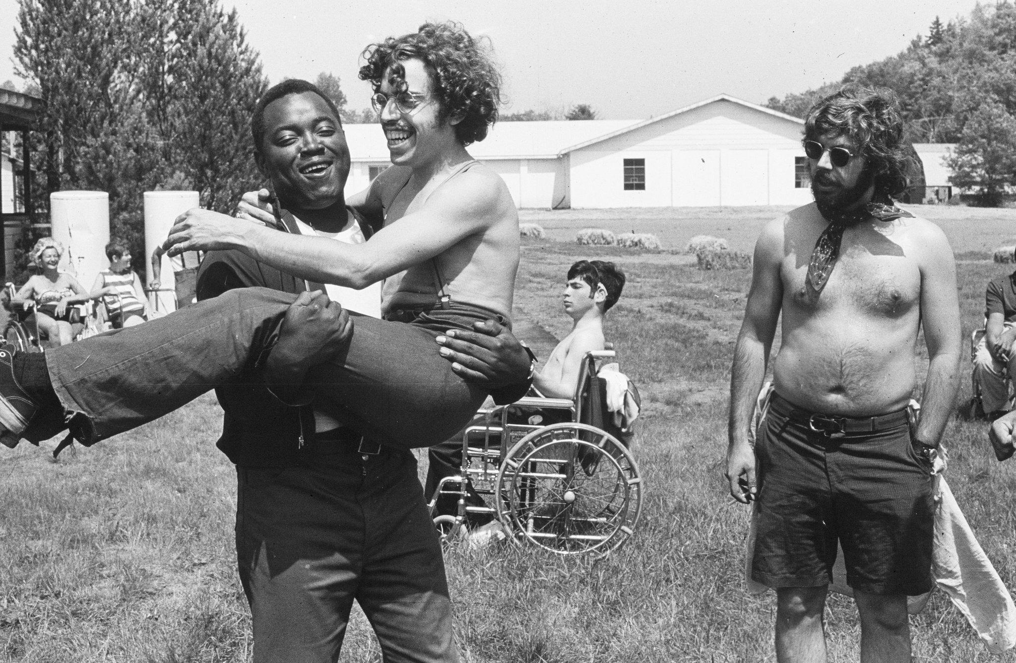Zwart-witafbeelding. Een verlamde jongeman in ontbloot bovenlijf wordt door een vriend gedragen. Ze lachen.