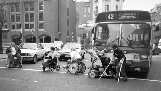Zwart-wit foto van vier mensen in een rolstoel en één persoon met krukken die op een drukke straat een rij auto's en een bus geblokkeerd houden