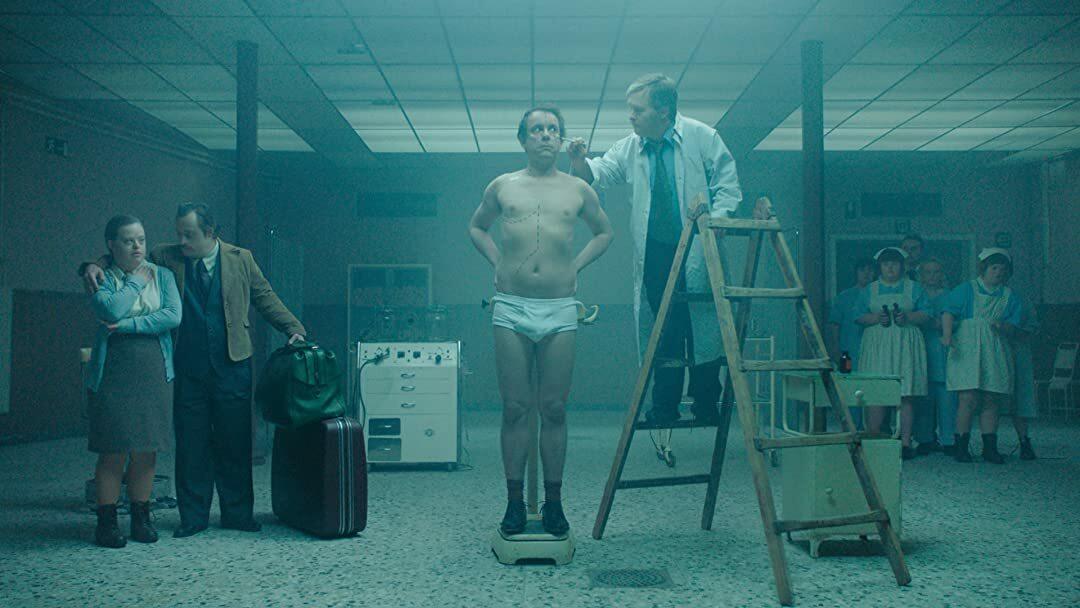 Een man in onderbroek wordt onderzocht door een dokter, die op een ladder staat. Op de achtergrond staan zijn ouders en een groep verpleegsters. Iedereen kijkt bezorgd.