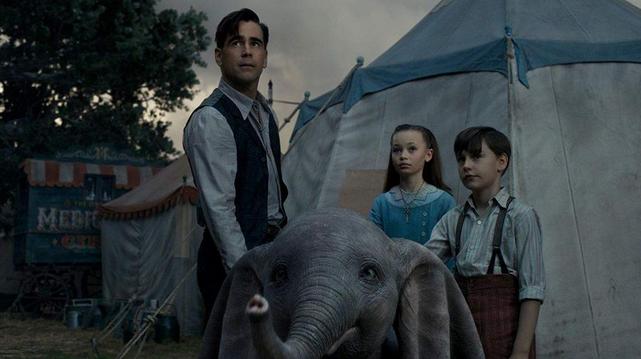 Dumbo en de drie hoofdrolspelers, twee kinderen en hun vader, kijken naar de lucht. op de achtergrond zie je een witte circustent