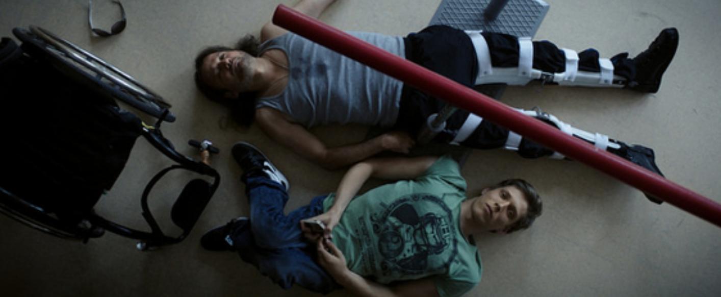Zolika en Rupaszov liggen op de grond. Naast hen staat een rolstoel.