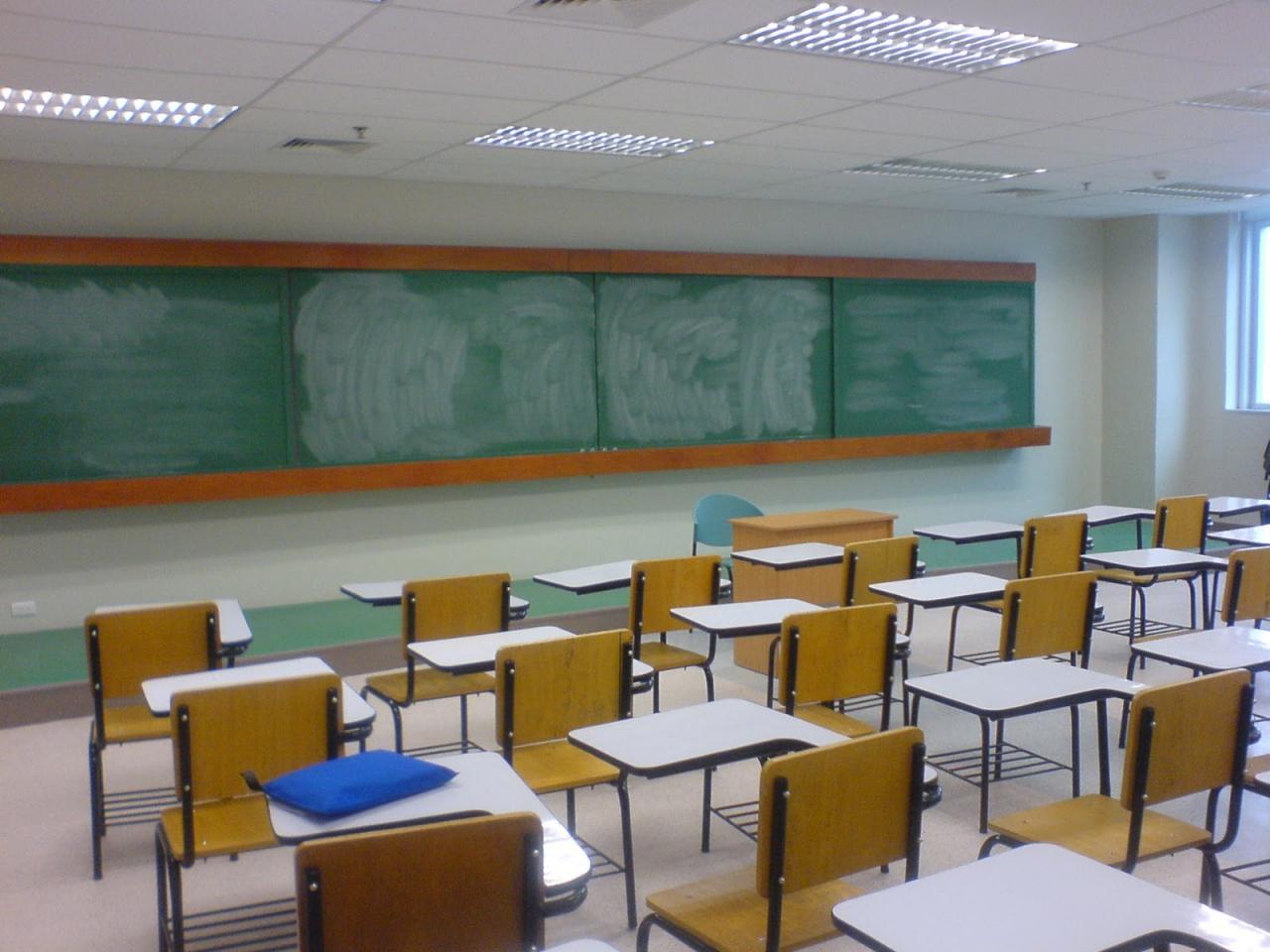 Foto van een leeg klaslokaal met een afgeveegd krijtbord. op één van de lessenaars ligt een blauwe map.