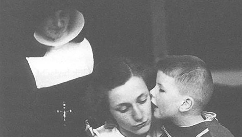 Zuster Gaudia (Ida Frye, linksboven) kijkt toe terwijl een medewerker van het Paedologisch Instituut Nijmegen met Siem, een jongen met autisme, aan het werk is