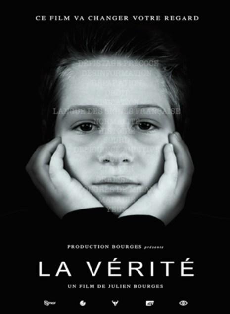Een jongen van 9 jaar houdt in close up zijn gezicht tussen zijn twee handen en kijkt de camera indringend aan