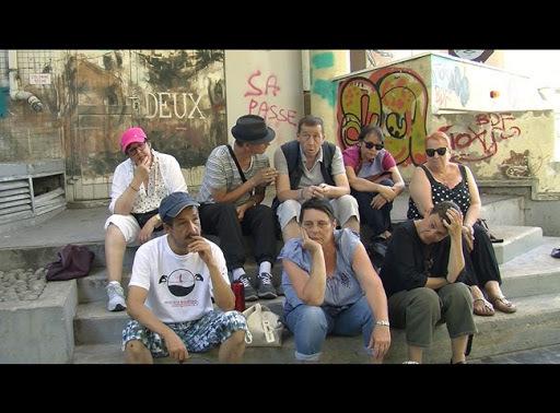 Een groep mensen zit op trappen in de stad, op de muren achter hen staat grafitti. Ze kijken serieus.