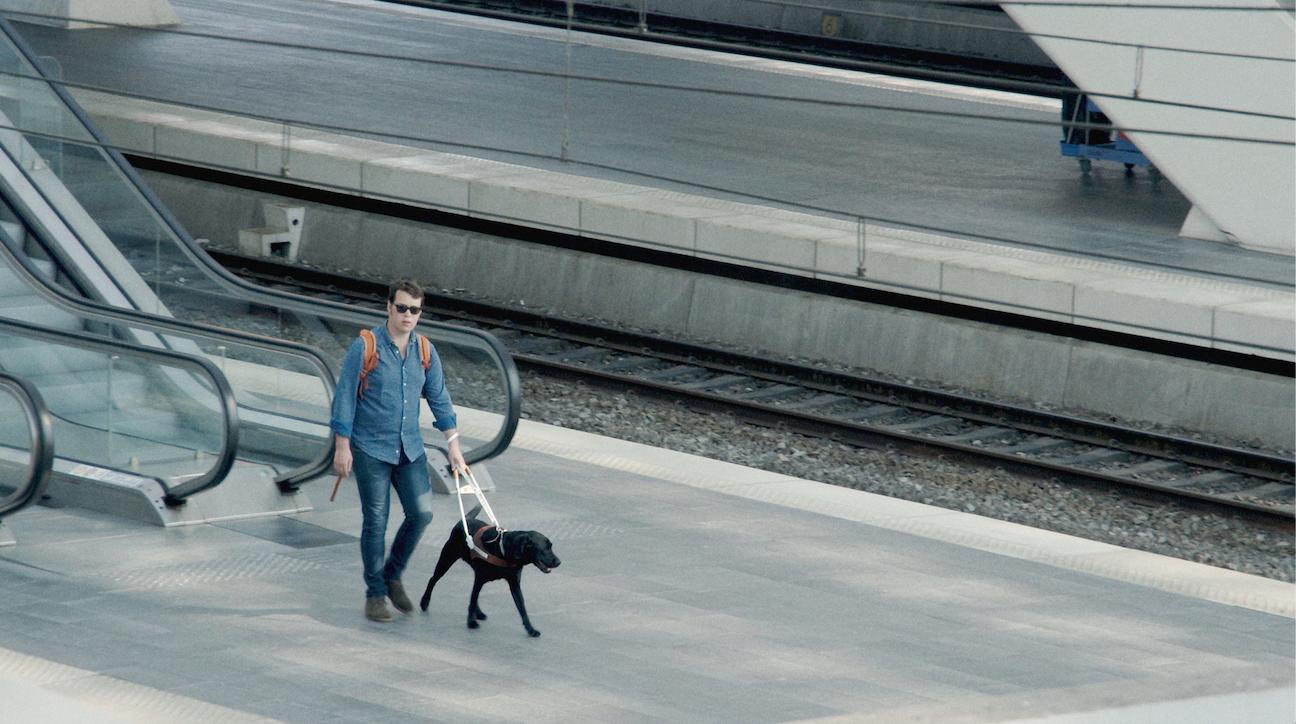 Victor loopt met zijn zwarte blindgeleidehond op het perron van het Luikse treinstation