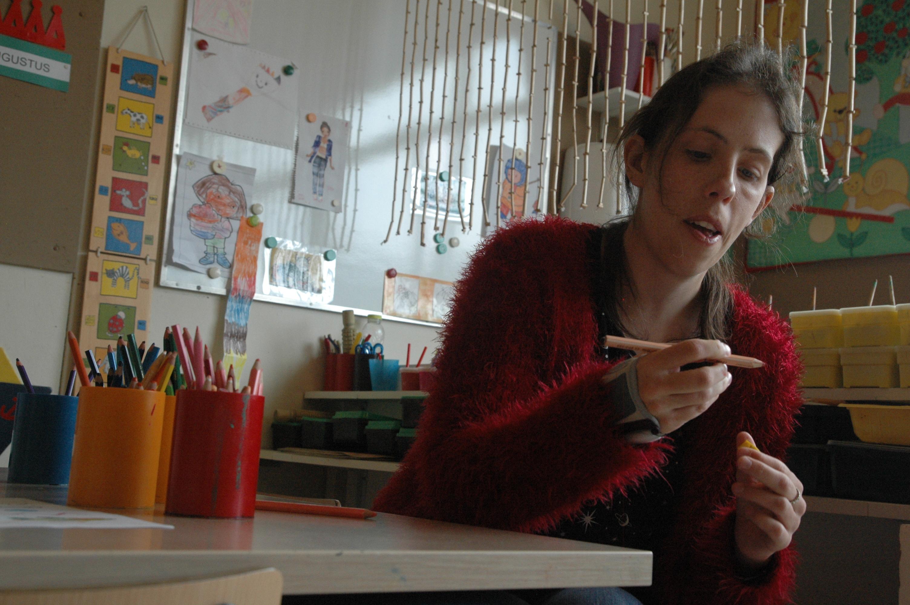 Een vrouw in een rode trui zit aan een tafel. Ze heeft een kleurpotlood in haar hand, waar ze aandachtig naar kijkt. Voor haar op de tafel staan nog meer kleurpotloden en stiften.