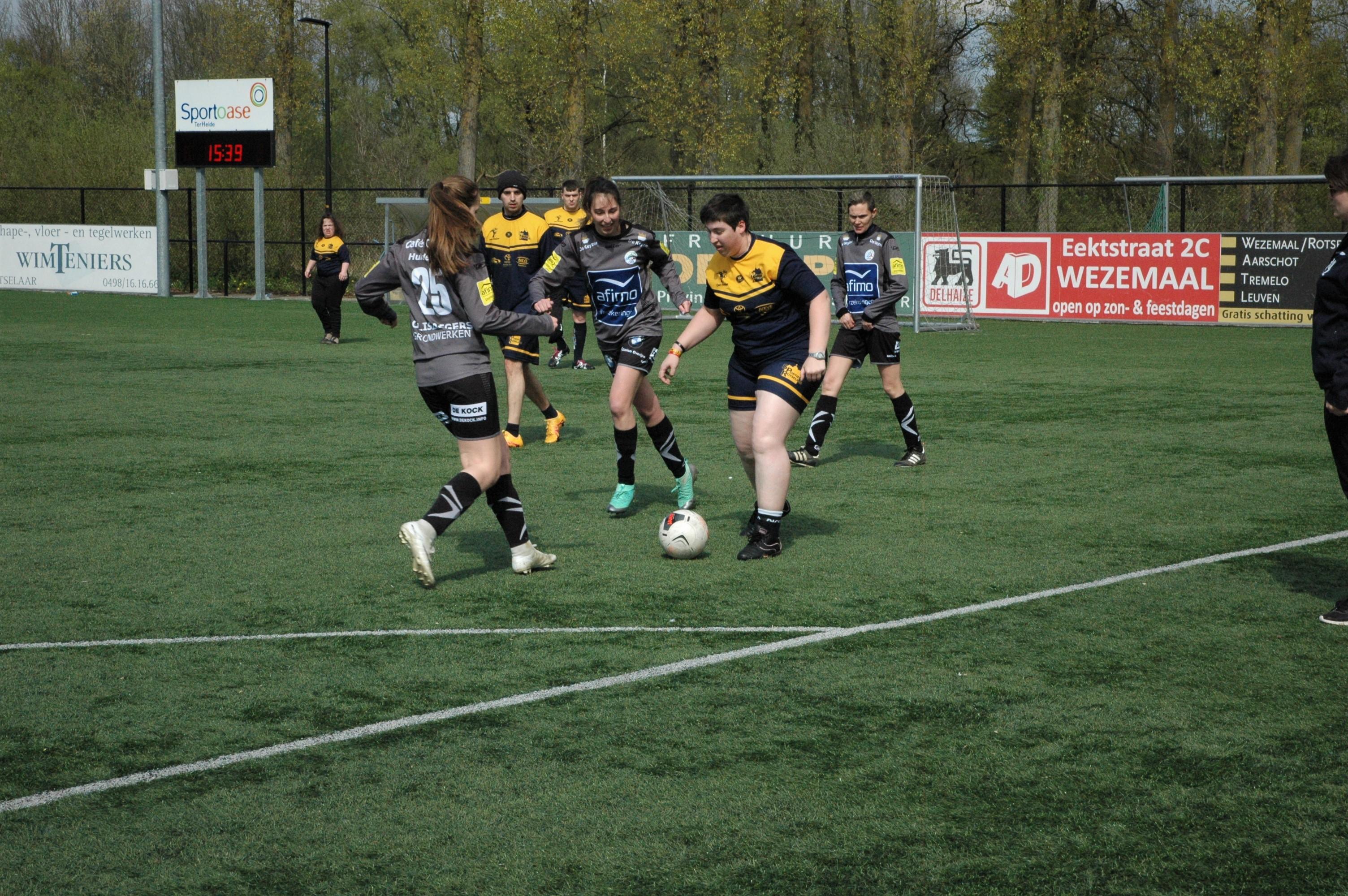 Een jongen en twee meisjes strijden om de bal tijdens een voetbalwedstrijd.