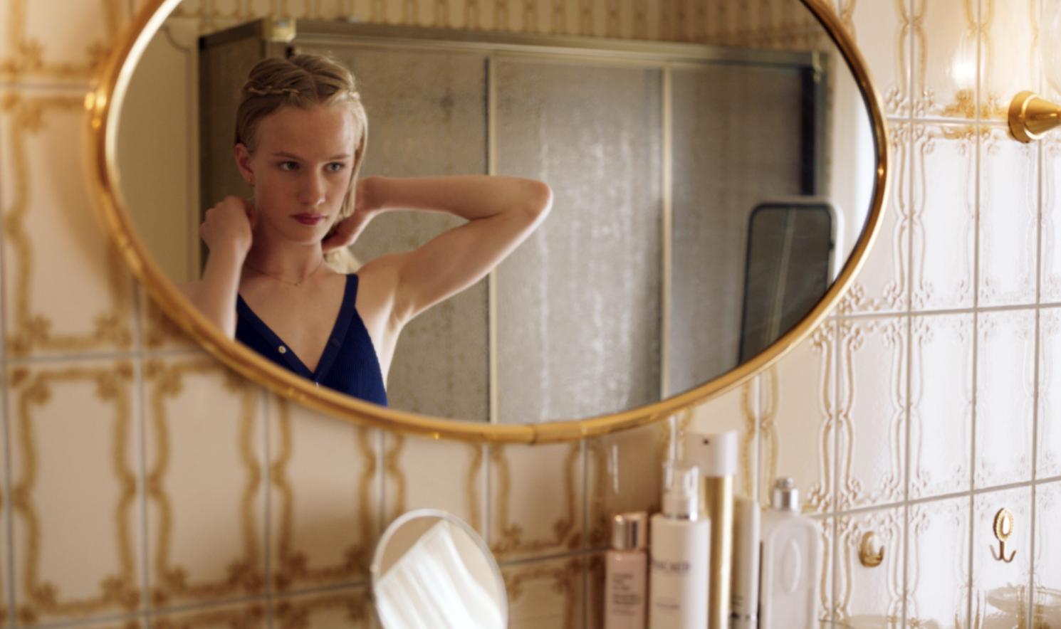 Lara staat voor de spiegel. Ze doet zichzelf een gouden kettinkje aan. Ze draagt een donkerblauwe jurk en heeft haar haar opgestoken.