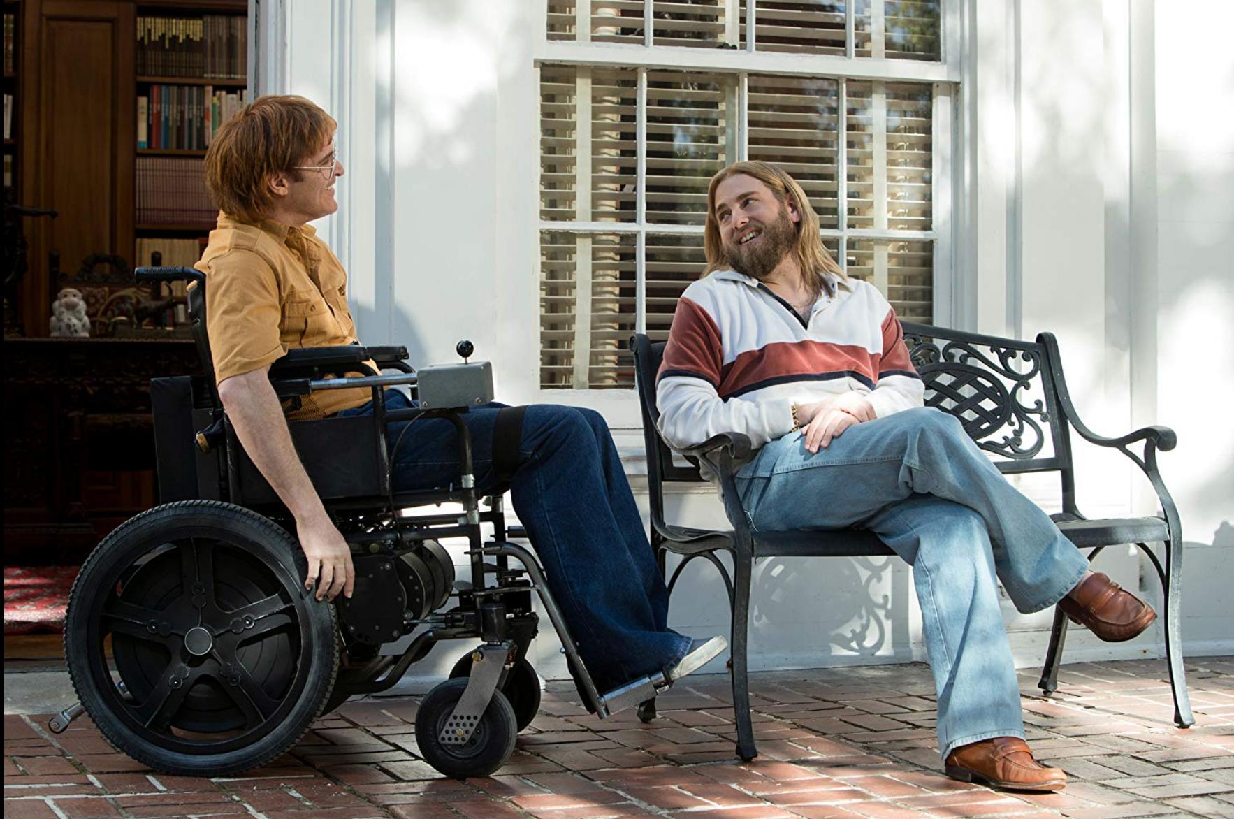 John zit in zijn rolstoel. Naast hem zit een man op een bankje. Ze lachen.
