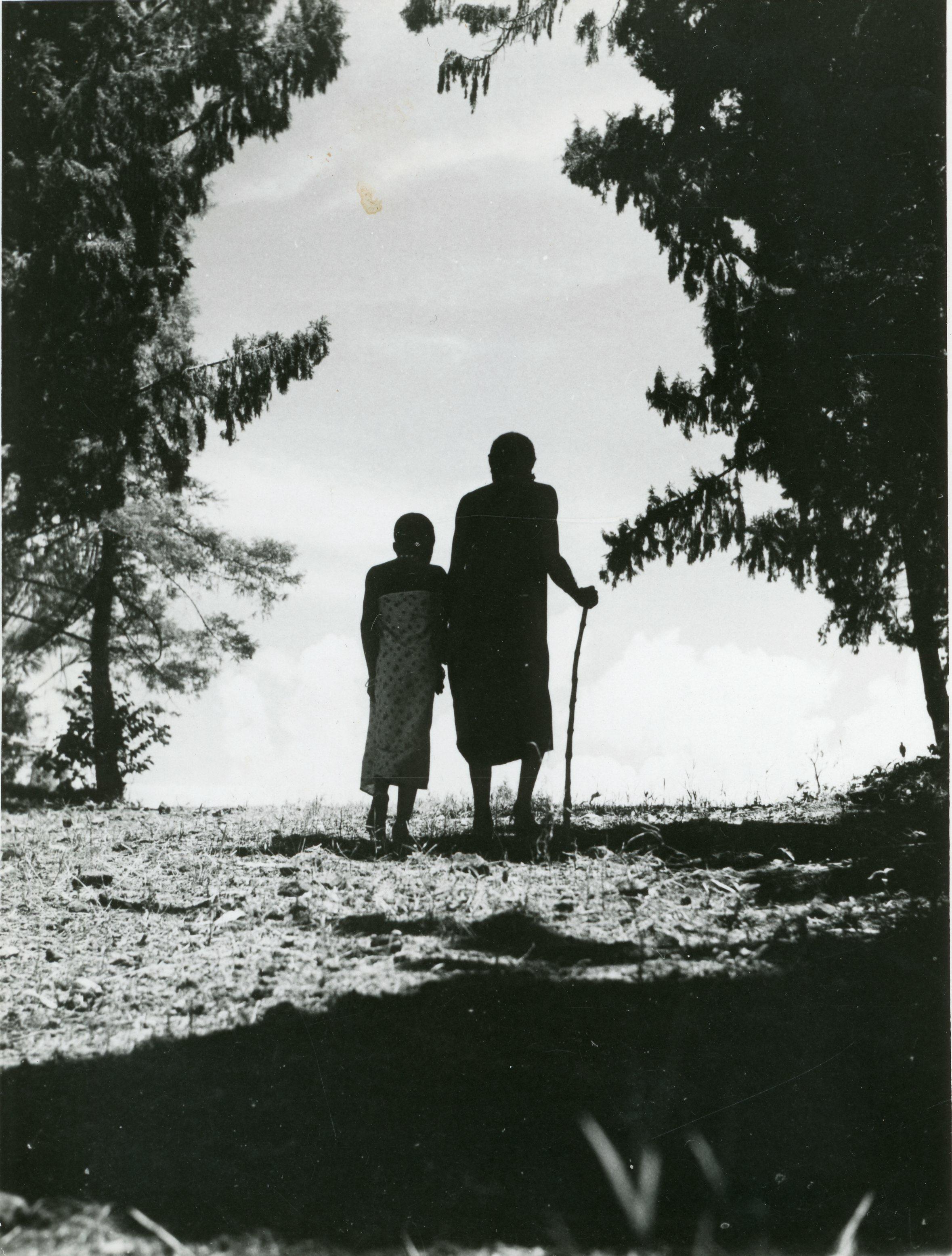 Zwart-wit afbeelding van Katutu. Hij wordt afgebeeld met een stok en wordt begeleid door een jongen