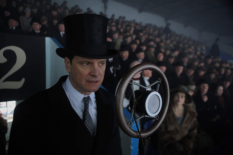Een man met een hoge hoed staat voor een microfoon. Op de achtergond zit een enorme massa toehoorders.