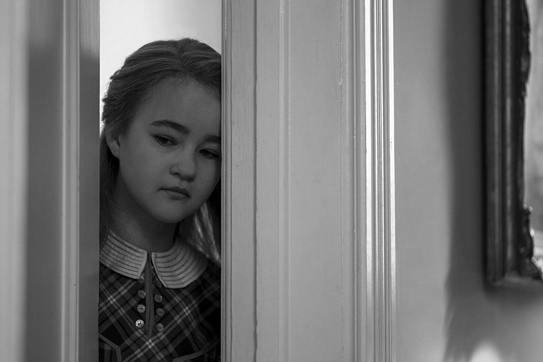 Rose staat in de deuropening met de deur op een kier. Haar hoofd rust tegen de deur.